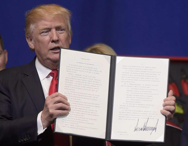 Donald Trump holds up an executive order he signed tightening the rules for technology companies seeking to bring skilled foreign workers to the U.S., on April 18, 2017