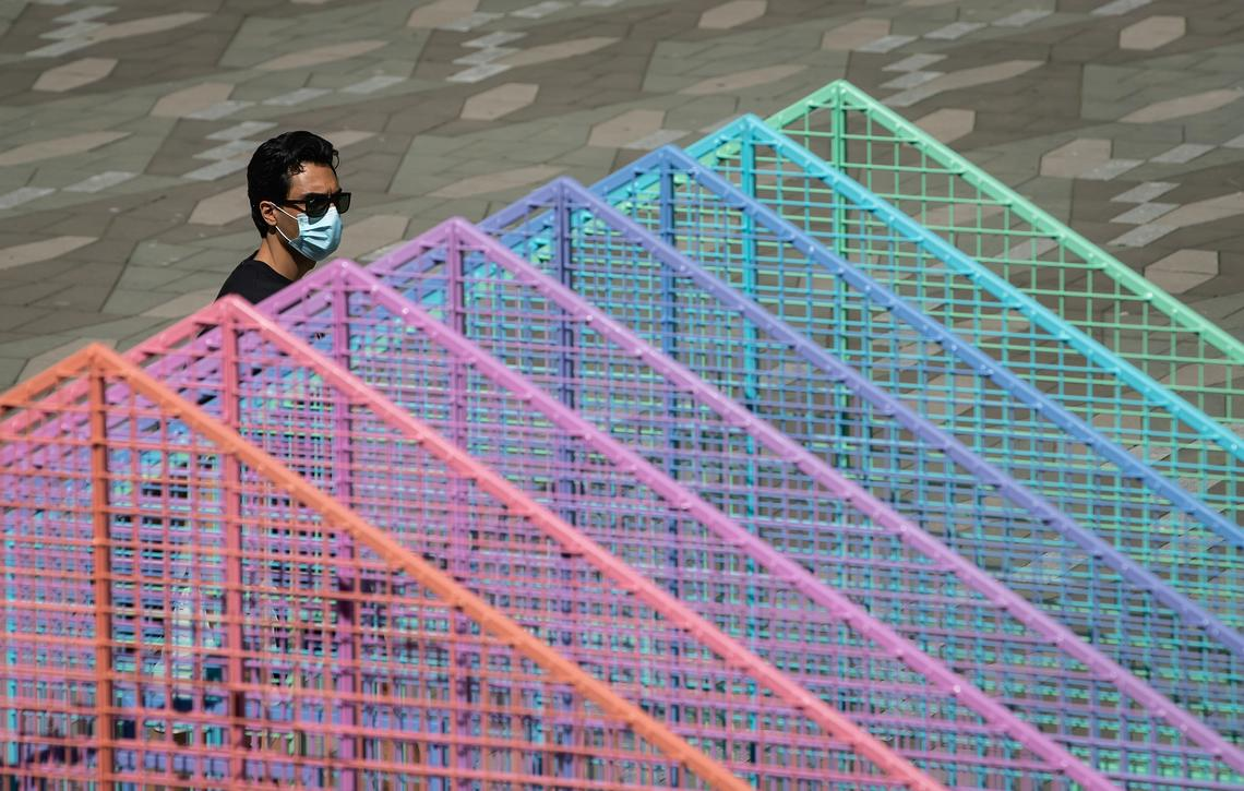 A man wearing a face mask to curb the spread of COVID-19 walks past a temporary Pride art installation in Vancouver on Aug. 3, 2020
