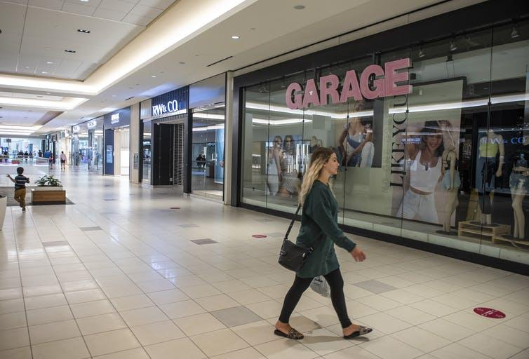 A shopper walks in the relatively empty Bayshore Shopping Centre mall in Ottawa on its first day open as part of Stage 2 of Ontario's plan to lift COVID-19 lockdowns.