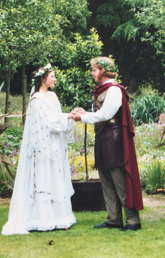 Alumnus Jonathan Love and an actress stand in front of a wooded area wearing Shakespearean garb. They are holding hands and both have flower crowns.