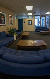 panorama of lounge space with blue couches and coffee tables