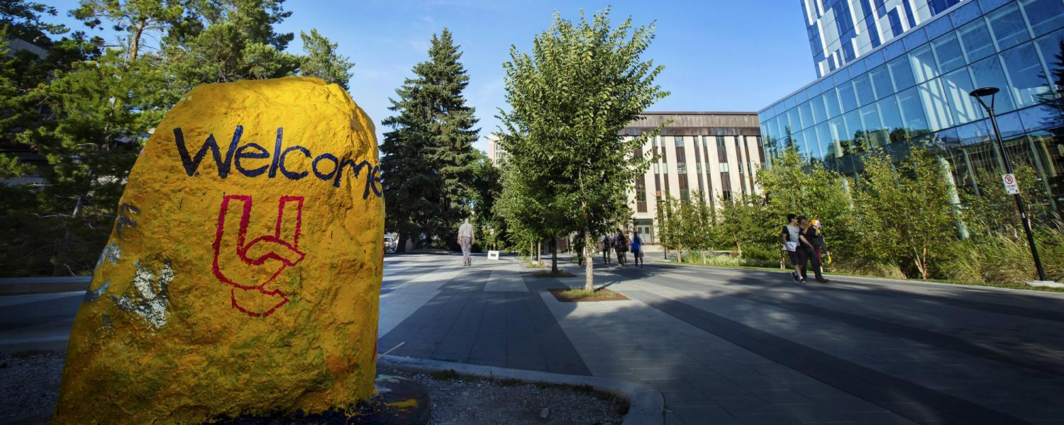 The rock is painted in UCalgary gold with welcome UC on it