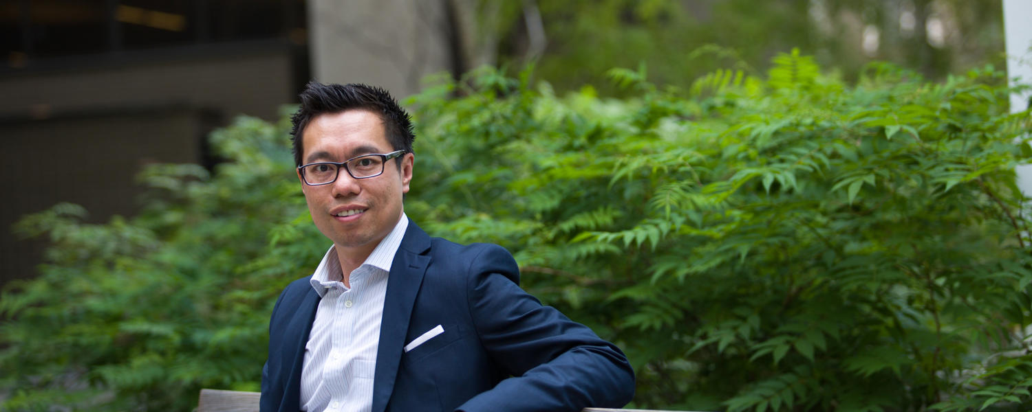 Andrew Szeto, sitting outside on a bench, was named Mental Health Director at the University of Calgary in 2016.