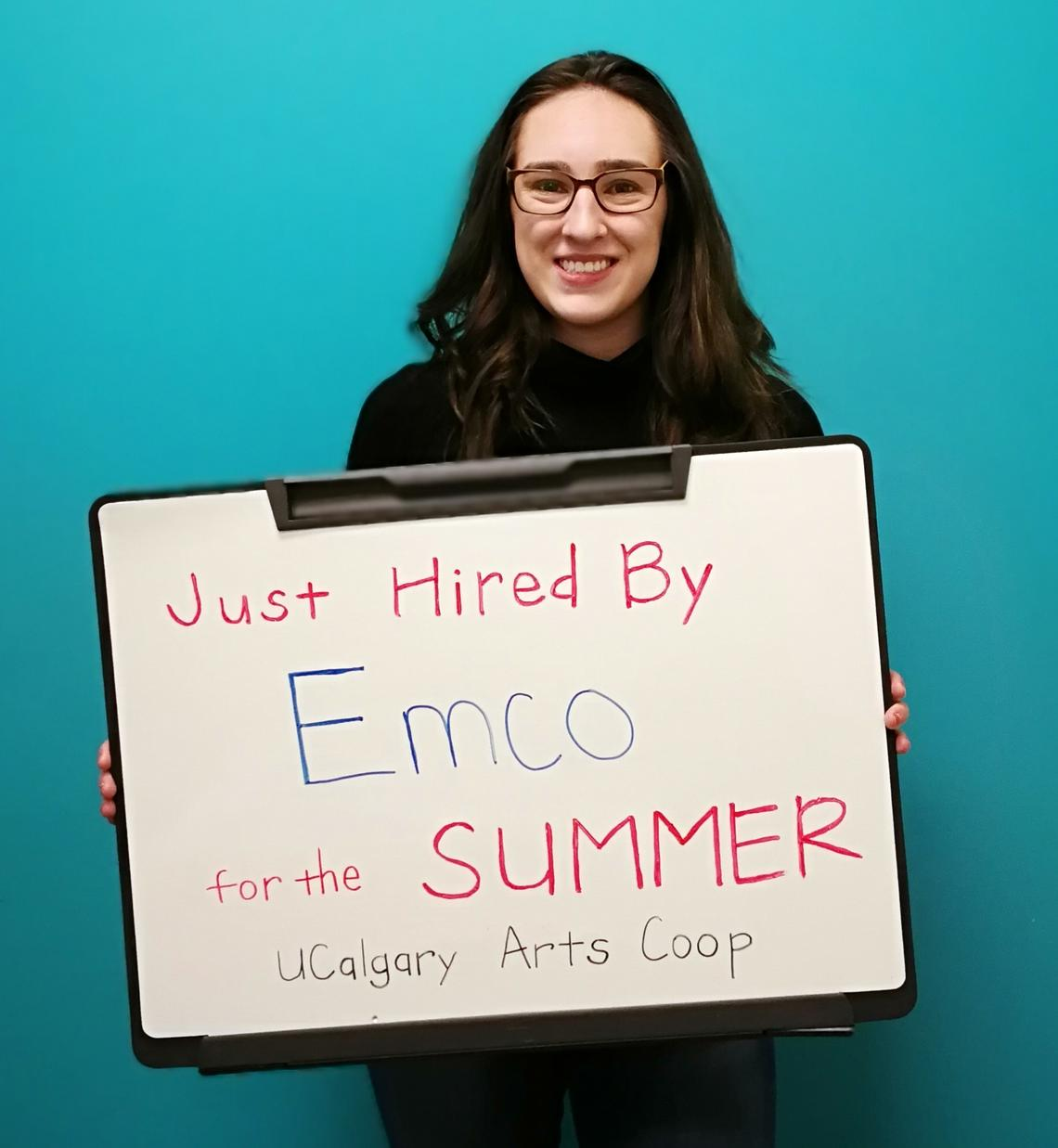 "A student holds a signboard that reads ""Just hired by Emco for the Summer"""