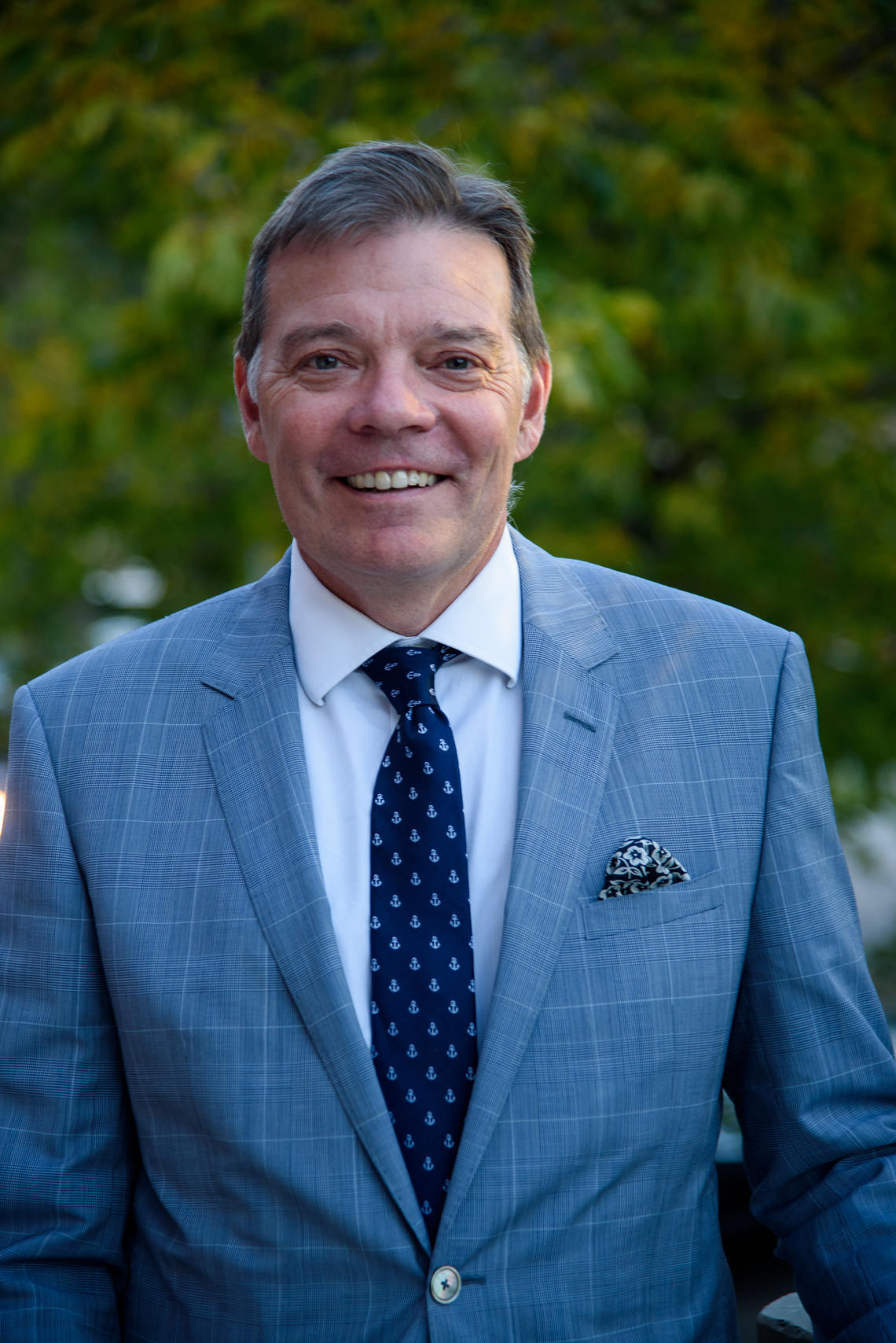 Faculty of Arts Dean Richard Sigurdson poses in a headshot. He is wearing a suit and smiling at the camera. Behind him is green foliage.