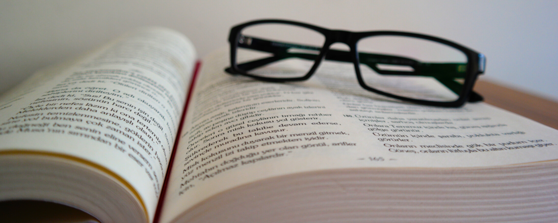 Stock image of an open book with glasses on it