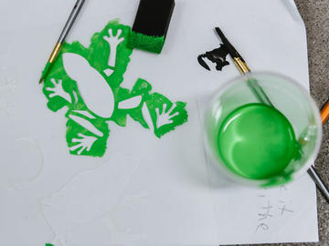 A green frog stencil with a cup of green paint beside it