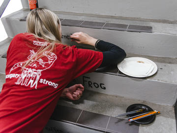 A volunteer wearing a red UCalgary Strong tshirt crouches as she paints a stair