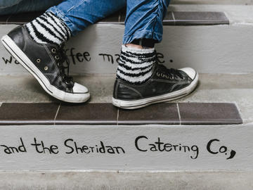 A pair of black leather Converse and striped socks stand on one of the steps