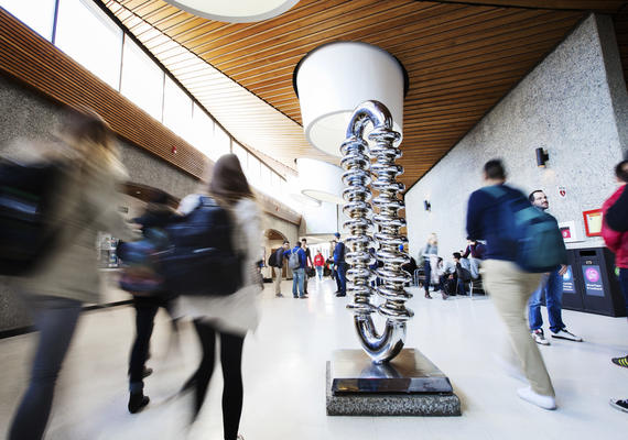 Katie Ohe's The Zipper sculpture is in the foreground in Science Theatres. Students walk on either side of it.