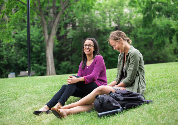 Two students sit on the lawn