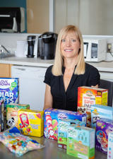 Charlene Elliott sits behind a row of colourful boxes of gluten-free food aimed at children