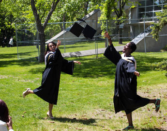 Two female students throw their convocation mortarboards in the air in celebration