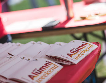 A stack of red and gold Alumni Weekend programs sits on a table