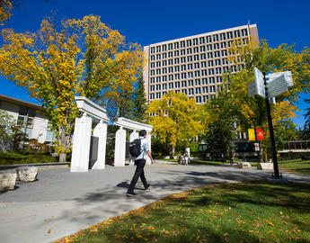 A student walks towards the Social Sciences building in early fall