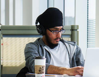 A student wearing a turban studies in the library