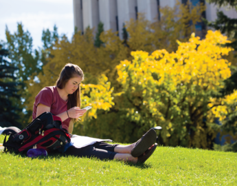 Student sitting in a field on campus